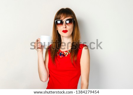 A young girl in a red dress holds in her hand a cup of coffee on a light background. Coffee shop concept, breakfast. #1384279454