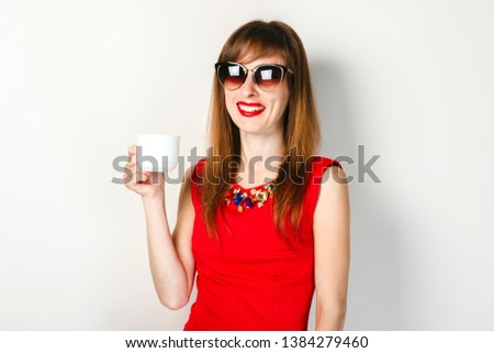 A young girl in a red dress holds in her hand a cup of coffee on a light background. Coffee shop concept, breakfast. #1384279460