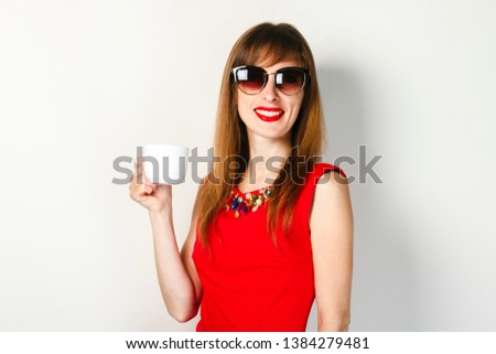 A young girl in a red dress holds in her hand a cup of coffee on a light background. Coffee shop concept, breakfast. #1384279481