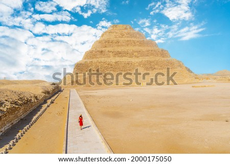 A young girl in a red dress walking in the Stepped Pyramid of Djoser, Saqqara. Egypt. The most important necropolis in Memphis. The first pyramid in the world Stock photo ©