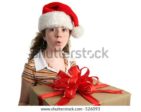 a young girl in a Santa hat amazed about a new Christmas gift.