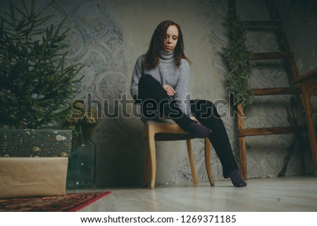 A young girl in a sweater posing against a gray wall. Woman dressed in warm sweater, street style clothing. Clean skin, long hair #1269371185