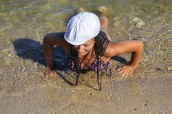 A young girl in a swimsuit is lying on the beach and trying to get up. Girl lies on her belly and looks at wet sand. Girl finished to swim