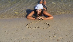 A young girl in a swimsuit lying on the beach and drawing a heart on the wet sand. Girl lies on her belly and looks at drawn heart. Enamored girl making love symbol on sand