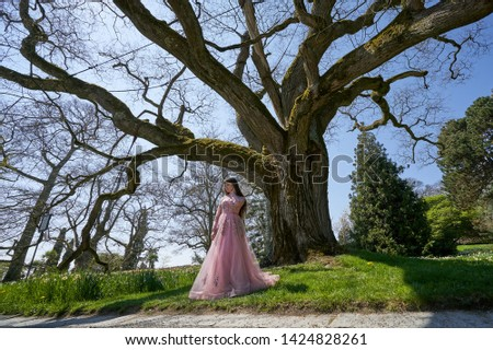 A young girl in a trendy lush pink dress stands next to a large Pogoda tree in a spring garden. Beautiful girl and Pogoda tree against the blue sky Zdjęcia stock ©