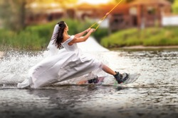 A young girl in a wedding dress riding on a wakeboard on the lake. Extreme bride. Unusual bride. An extraordinary bride.
