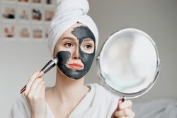 A young girl in a white bathrobe with a towel on her head holds a mirror in her hands and applies a natural black mask with activated carbon for problem skin, quarantine isolation, home spa treatments