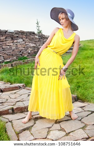 A young girl in a yellow dress in the park