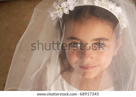 A young girl in her holy communion outfit looking at the camera from behind her veil. Stunning green eyes