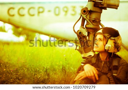 a young girl in military uniform sits near a military aircraft