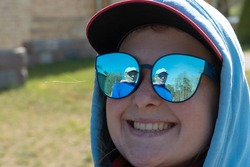A young girl in mirrored sunglasses. The man is reflected in the glasses. A beautiful girl with freckles on her face in a hood and cap with a wide smile and snow-white teeth.