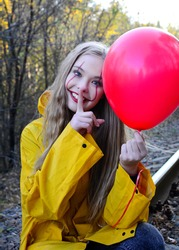 A young girl in the image of an evil clown with a red ball in her hands sits on the rails on an abandoned railway. Vertical