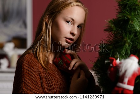 a young girl in the next to the white fireplace, decorate a Christmas tree with toys  #1141230971