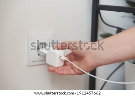 A young girl inserts a plug into an outlet. Young woman plugs the phone charger into the socket. High quality photo