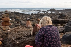 A young girl is adding some finishing details to a mini rock sculpture of a person. What better way to spend time on the beach in Autumn.