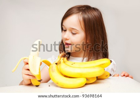 A young girl is eating a delicious looking yellow banana.  She looks like she is enjoying herself.