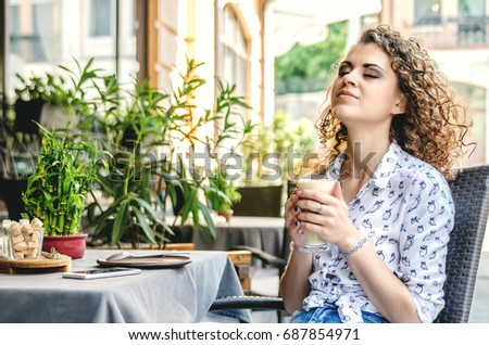 A young girl is enjoying coffee sitting in a cafe on the summer terrace.
