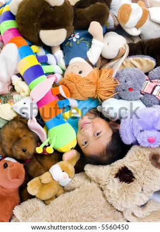 A young girl is in the middle of a big pile of stuffed animals.