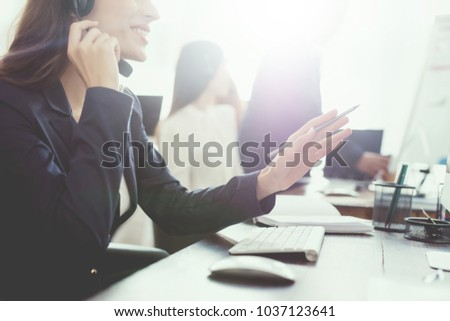 A young girl is looking at a computer screen in the office and is talking on the phone. She works in the call center. She's in a good mood. Call center concept. #1037123641