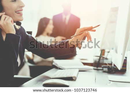A young girl is looking at a computer screen in the office and is talking on the phone. She works in the call center. She's in a good mood.