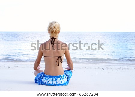 A young girl is meditating on the beach.