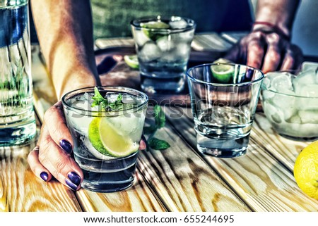 A young girl is preparing an alcoholic or non-alcoholic cocktail. hands, bartender, bar, restaurant, mint, lime, lemon, alcoholic, non-alcoholic #655244695