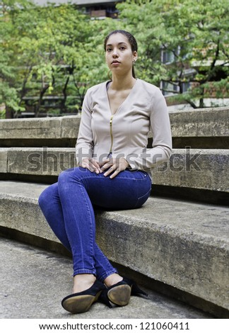 A young girl is sitting on stairs./Portrait of Young Girl