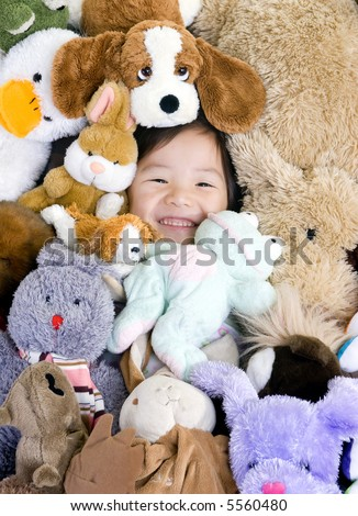 A young girl is surrounded by her stuffed animals.