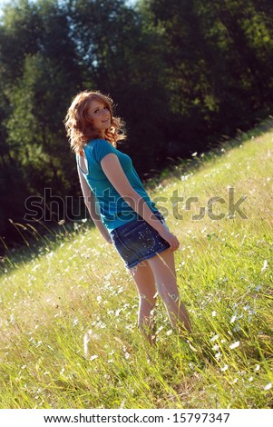 A young girl is walking outside in a field of grass.  She is smiling at the camera.  Vertically framed shot.