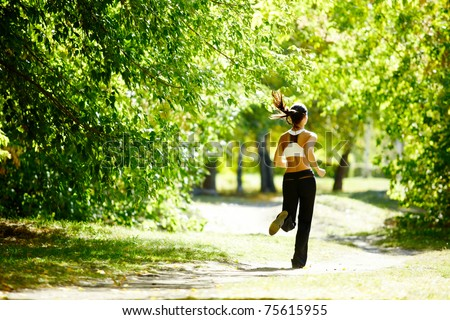 A young girl jogging in the park along trees