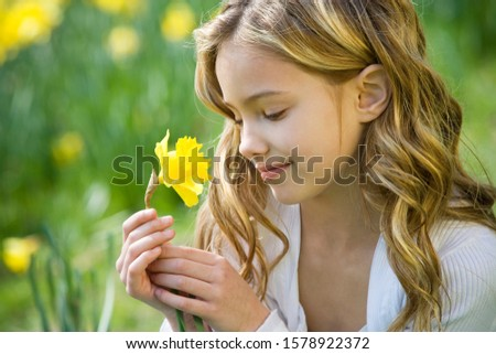 A young girl looking at a daffodil