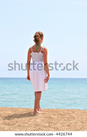 A young girl looking out at the beach - stock photo