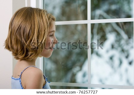 a young girl looking out the window, excited to see snow outside.