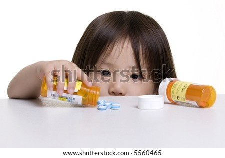 A young girl looks at a pile of pills that was left on a counter.