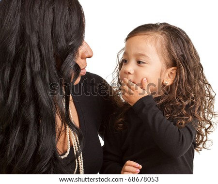 A young girl looks at her mother and begins to blow a kiss