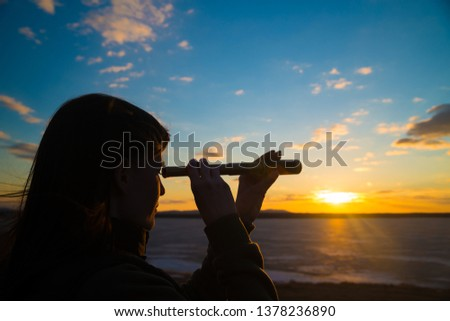 A young girl looks into a monocular telescope against a dramatic sky in the sunset. business concept idea, look to the future, look, spy. Businessman. Vision