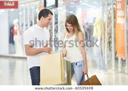 A young girl looks into the shopping bag with men