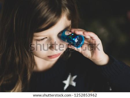 A young girl looks through a kaleidoscope