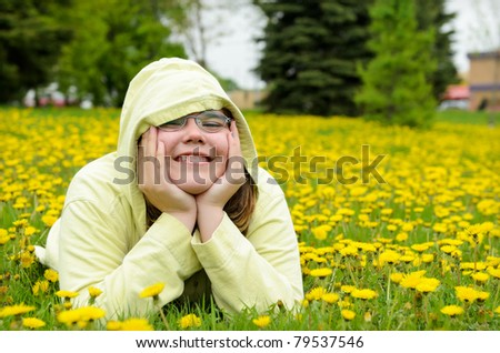A young girl lying in a field of dandelions.