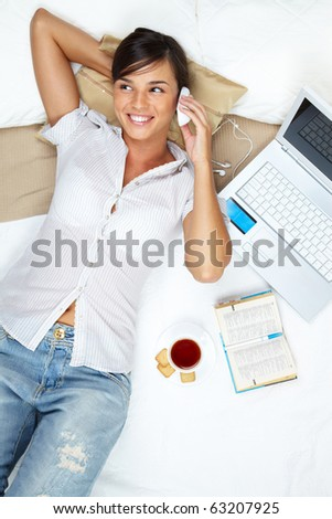 A young girl lying in bed and talking on her mobile phone