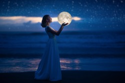 A young girl on a night beach holds the moon, with a starry sky. Art photography