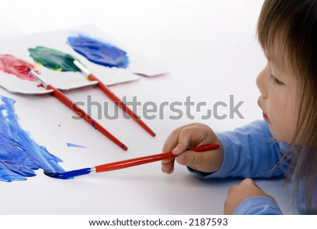 A young girl painting her masterpiece on the floor