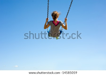 A young girl playing on a swing-set in front of a blue sky.  Girl is swinging very high in swing, with copy space