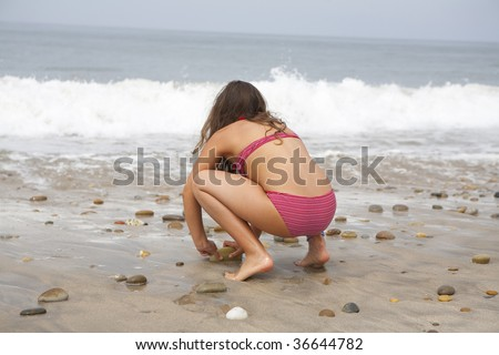 a young girl playing on the beach with sand and water