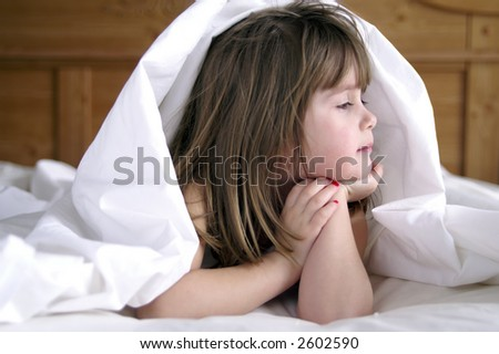 A young girl playing under the sheets on her bed
