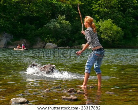 A young girl plays with dog at river.