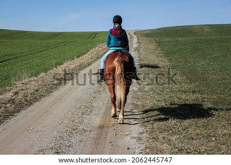 A young girl rides a horse down a dirt road holding the reins.