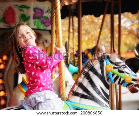 a young girl riding on a merry go round at the zoo