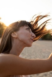 A young girl shakes her head with her hair tousled in the wind. A beautiful girl with dark hair fluttering in the wind.