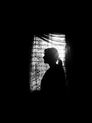 A young girl silhouetted against the window